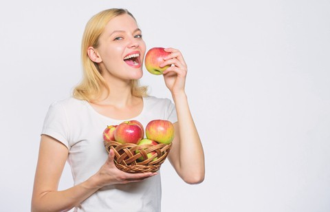 woman to eat apple - foods for healthy teeth and gums image